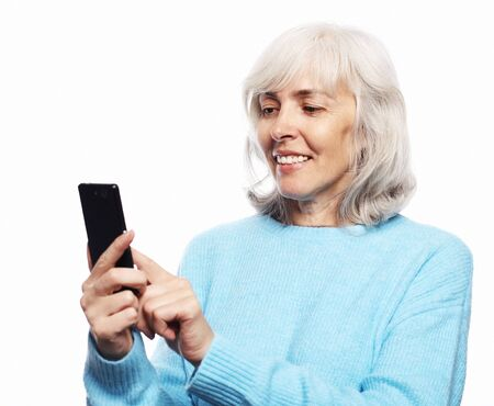 Lifestyle, tehnology and people concept: eldery woman with smartphone Фото со стока