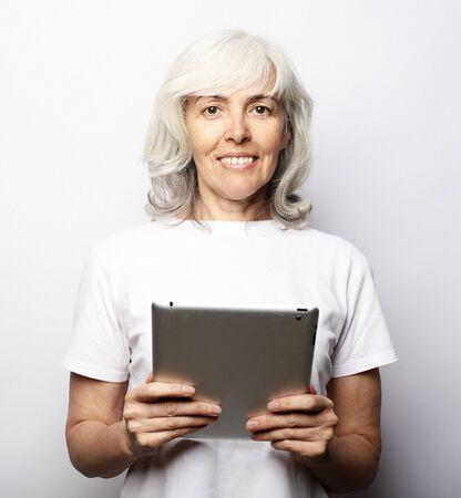 Senior happy woman using ipad isolated on white background 版權商用圖片