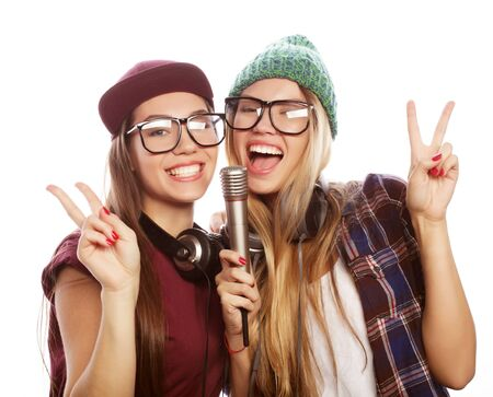 lifestyle, happiness, emotional and people concept: two beauty girls with a microphone singing and having fun