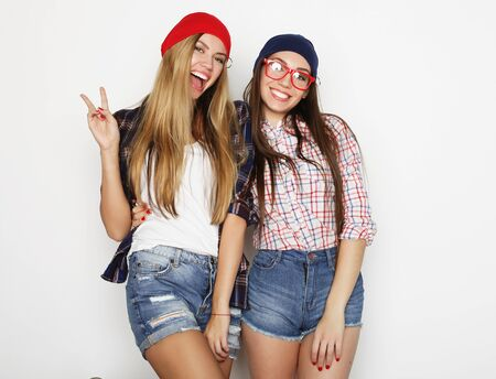 lifestyle, friendship and people concept: Two young girl friends standing together and having fun. Hipster style. Zdjęcie Seryjne - 129251578