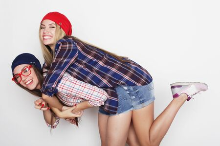 lifestyle, friendship and people concept: Two young girl friends standing together and having fun. Hipster style.