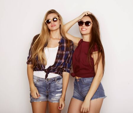 lifestyle, friendship and people concept: Two young girl friends standing together and having fun. Hipster style. Zdjęcie Seryjne - 129251631