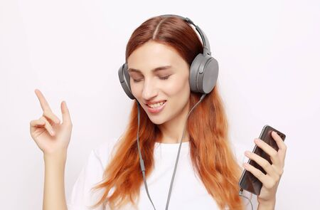 Beautiful young woman in headphones listening to music on white background Zdjęcie Seryjne