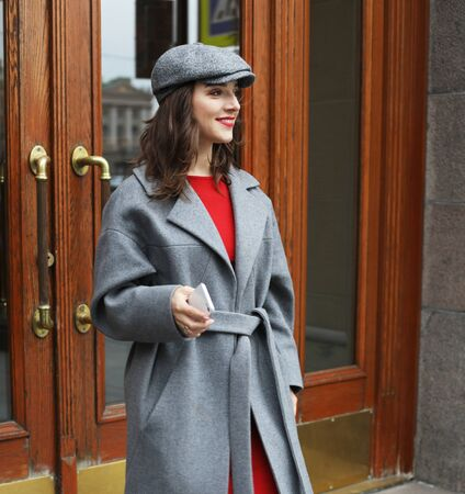 young stylish pretty woman wearing red dress, grey coat and hat posing in the city streets. Stock fotó
