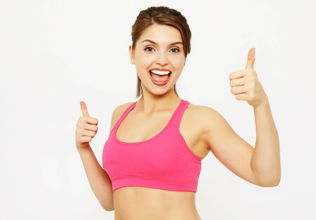 Portrait of a young fitness woman showing ok sign isolated on a white background Stockfoto