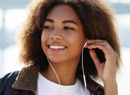 lifestyle concept: Young african american girl using mobile phone and headphones, smiling