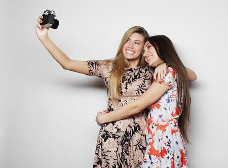 friendship and people concept: Two young girl friends standing together and take photo with camera