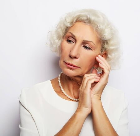Thoughtful serious senior woman feeling blue worried about problems