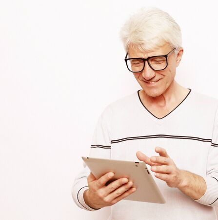 Gray-haired elderly man communicates with his family on a tablet