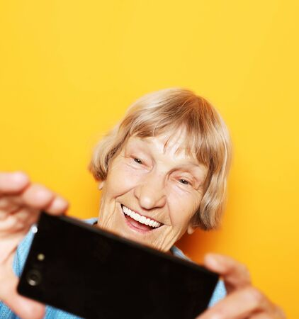 lifestyle, tehnology and people concept: grandma in blue sweater smiles and takes a selfie