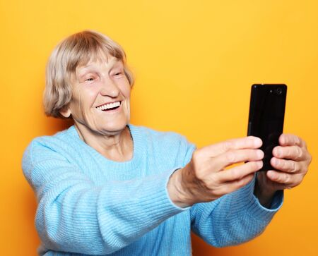 grandma in blue sweater smiles and takes a selfie over yellow background Фото со стока