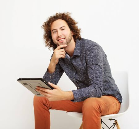 happy casual man on a chair with a tablet pc,