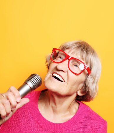 lifestyle and people concept: Portrait of funny grandmother wearing pink sweater holds up the microphone Zdjęcie Seryjne