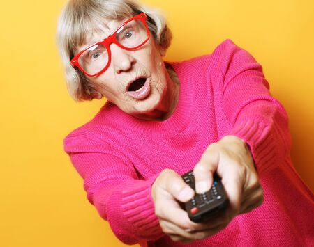 lifestyle, tehnology and people concept: funny grandmother is holding a TV remote over yellow background Zdjęcie Seryjne