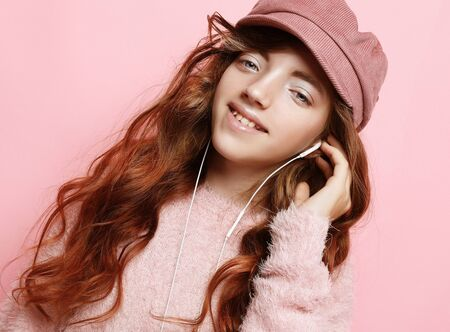 Image of happy teen girl standing isolated on pink background, in pink hat and sweater.