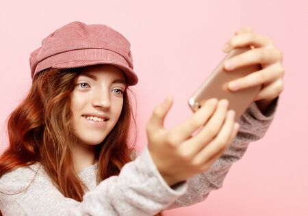 little girl with curly hair l taking a selfie isolated over pink background