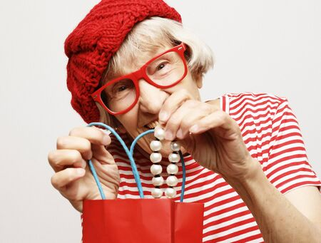 lifestyle and people concept: elderly woman pulls out a gift from the bag