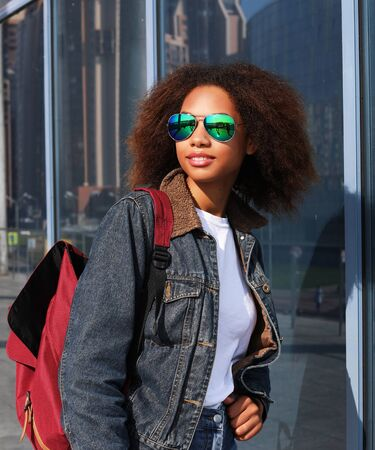 lifestyle and people concept: Young black woman with backpack on the street