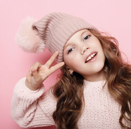 People, childhood and fashion concept: little girl child wearing pink winter hat and sweater over pink background