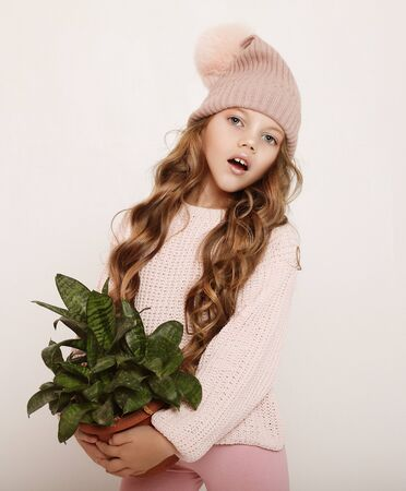 Beauty and fashion concept: Little girl wearing pink outfit and holding flower