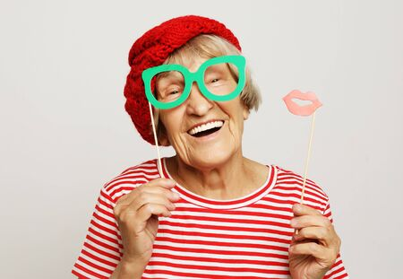 funny grandmother wearing red clothes holding falce glasses and ready for party 写真素材 - 129274688