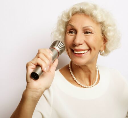 lifestyle and people concept: Portrait of charming modern grandmother holds up the microphone