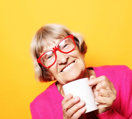 Portrait of old excited lady smiling laughing, holding cup drinking coffee, tea