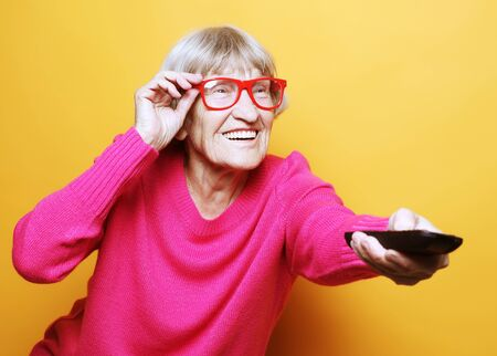 lifestyle and people concept: funny grandmother is holding a remote tv 写真素材