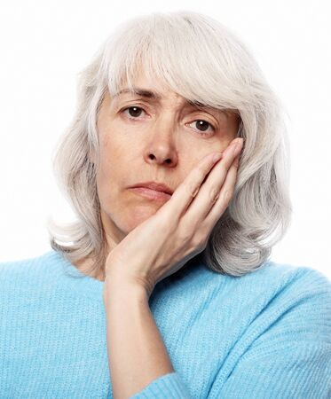 Lifestyle, health and people concept: Elderly woman suffering from toothache on white background