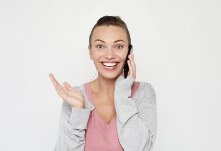A beautiful young blonde woman picks up the news on the phone and is surprised.