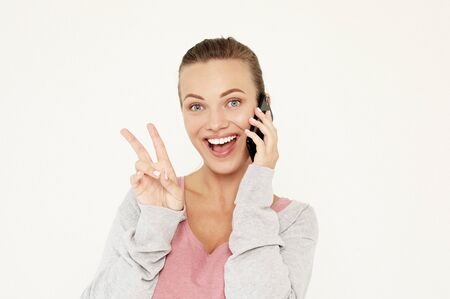 A beautiful young blonde woman picks up the news on the phone and is surprised. Stockfoto - 130312346