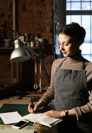 Young brunette woman writes to notebook in sewing workshop, handmade concept 版權商用圖片