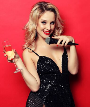 woman in black evening dress holding glass of champagne and microphone.