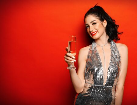 New Year, Birthday, holiday concept: Young attractive brunette woman in evening dress holding glass of champagne.