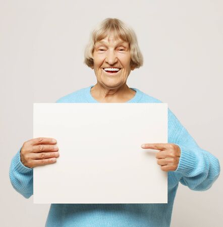 Aged woman with blank advertising board or copy space. Stock fotó