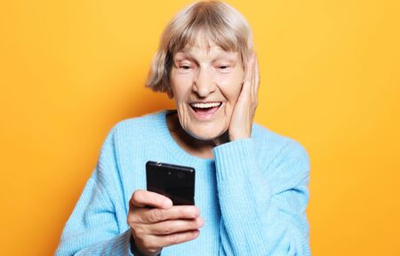 lifestyle, tehnology and people concept: old granny looks at her smart phone and is surprised
