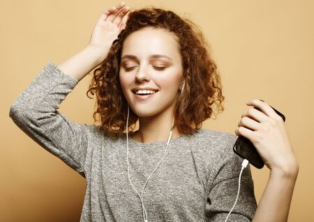 lifestyle and people concept: young woman in headphones listening to music smiling with closed eyes Stock fotó