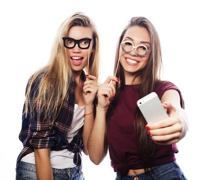 two young women with party glasses taking selfie with mobile over white background