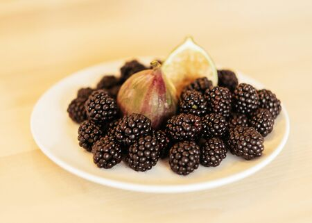 Blackberry and fig on a white plate close-up Banque d'images
