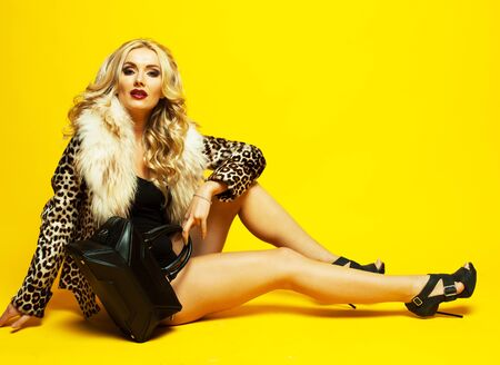 Adorable blonde in a fur jacket, holds a bag and posing. Fashionable concept. Yellow Background.