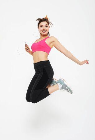 belle jeune femme en vêtements de sport sautant sur fond blanc, concept sport Banque d'images