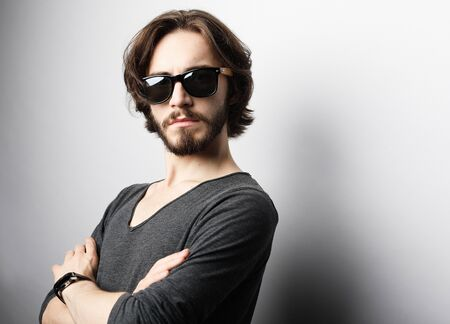 Fashion and people concept: portrait of a young man wearing sunglasses on light grey background