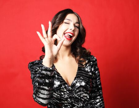 Portrait of a pretty brunette woman in evening dress showing okay sign over red background