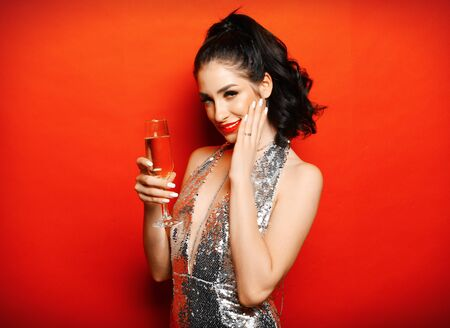 luxury woman in evening dress posing over red background