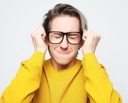 Waiting for special moment. Portrait of young man wearing yellow sweater and glasses