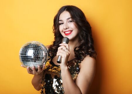 woman in evening dress holding microphone and disco ball over yellow background