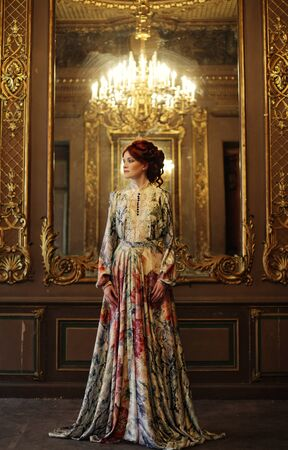 beautiful woman standing in the palace room with mirror.