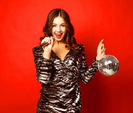lifestyle and people concept - woman in evening dress holding microphone and disco ball Archivio Fotografico
