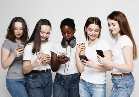 lifestyle, technology and internet concept: group of five women looking at their smartphones Foto de archivo