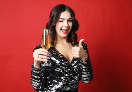 woman in black evening dress holding glass of champagne over red background